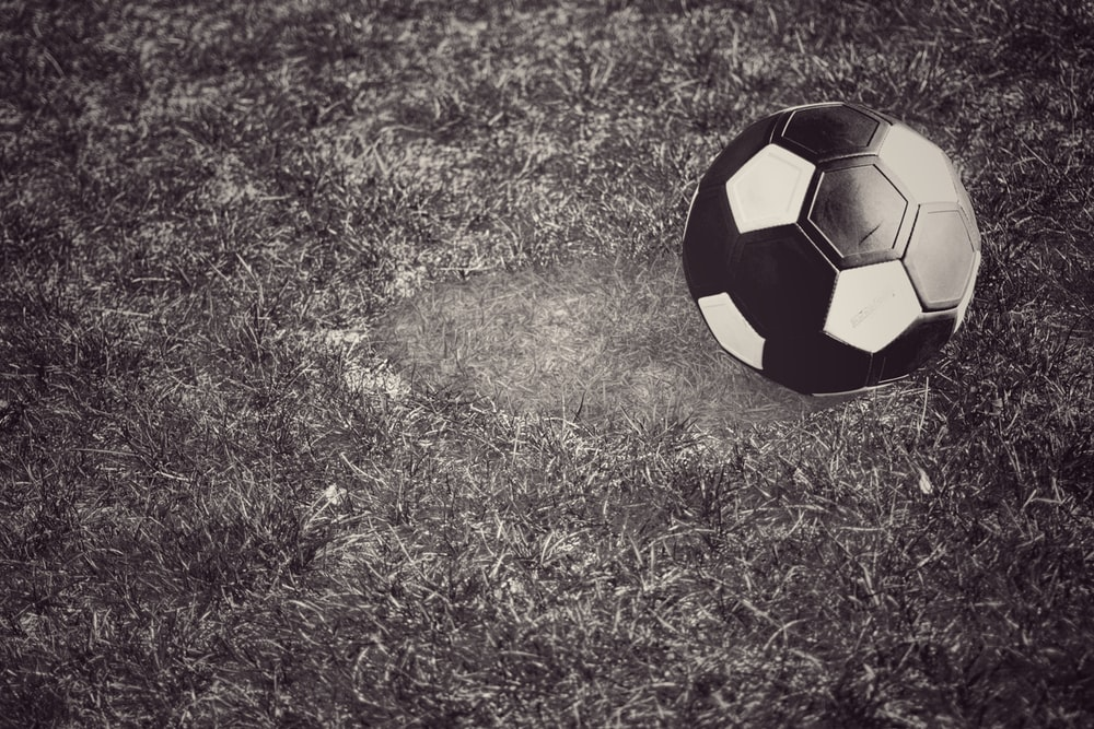 black and yellow soccer ball on green grass field