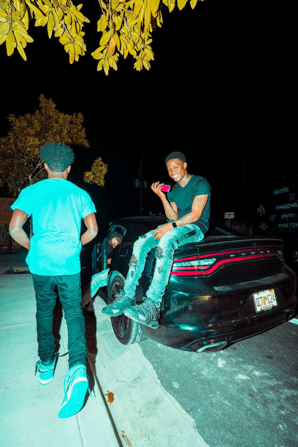 man in blue t-shirt and blue denim jeans standing beside black car during night time