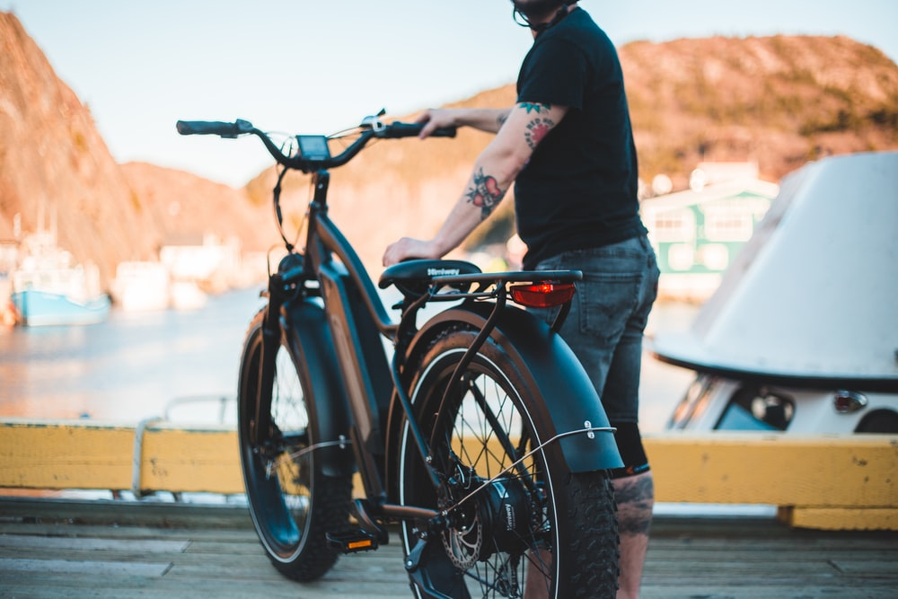 man in black long sleeve shirt and blue denim jeans riding on black bicycle during daytime