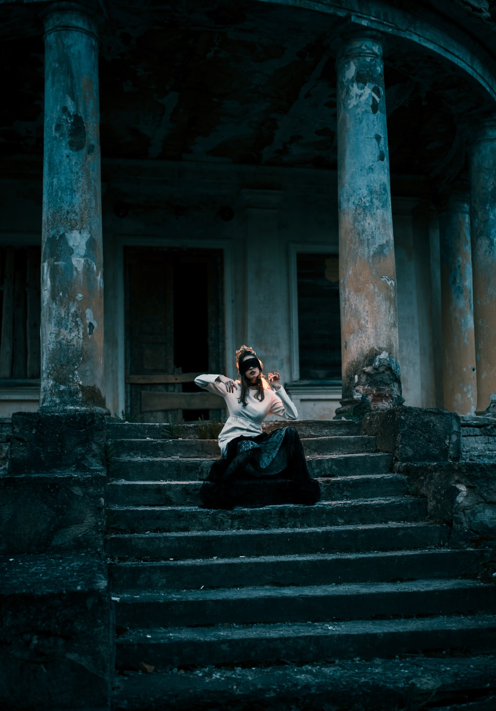 woman in black dress sitting on stairs