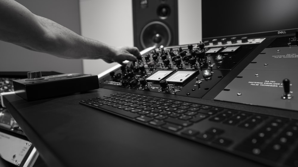 person holding black audio mixer