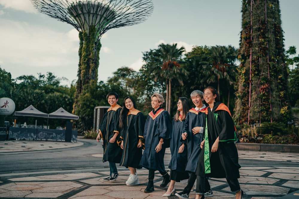 group of people in black academic dress standing on gray concrete pavement during daytime