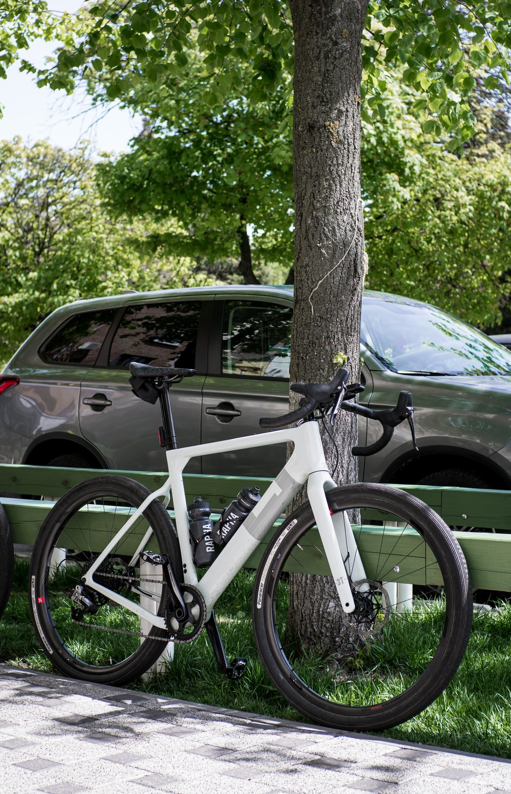 white and black mountain bike leaning on tree trunk