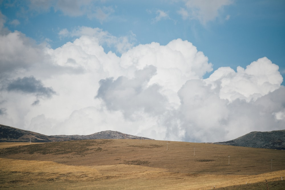 white clouds over brown field