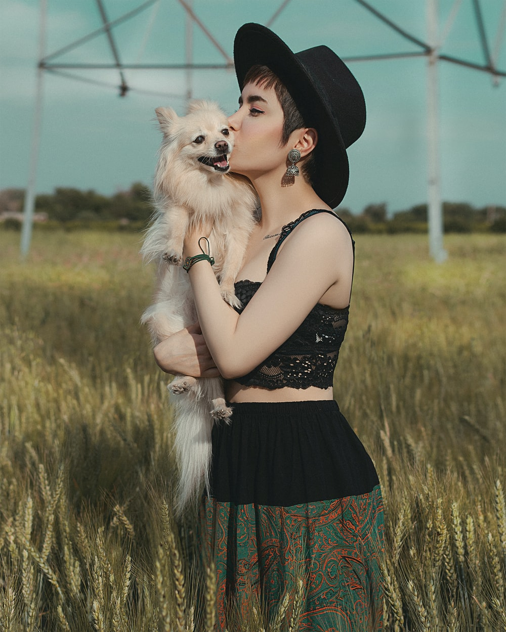 woman in black and red floral dress holding white long coated small dog