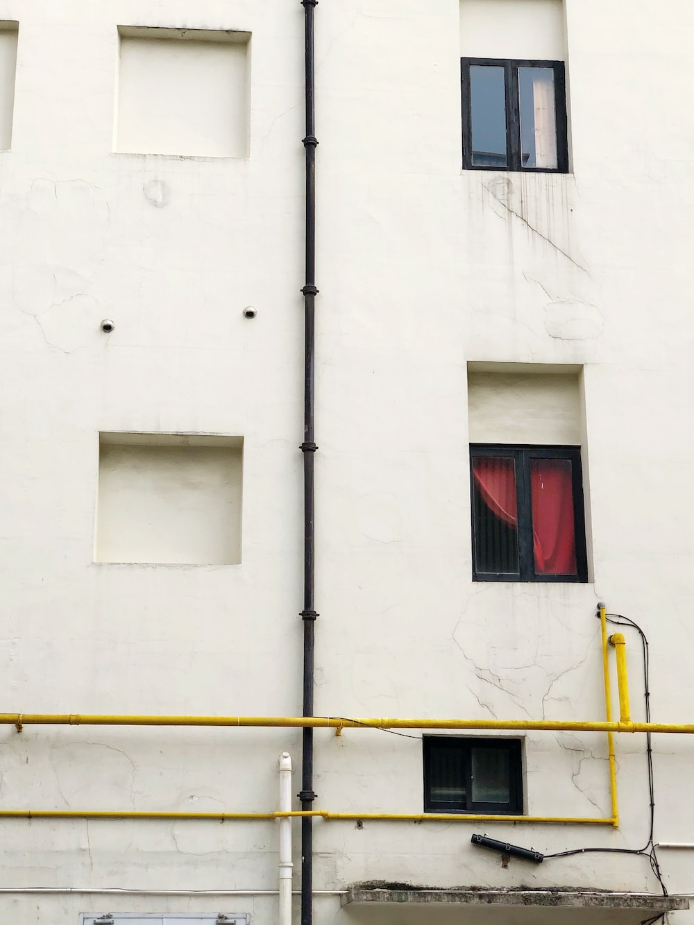 white concrete building with red window