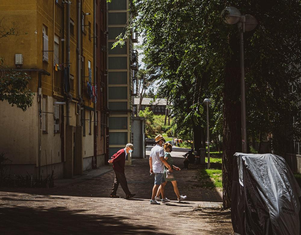 man in white t-shirt and brown shorts walking on sidewalk during daytime