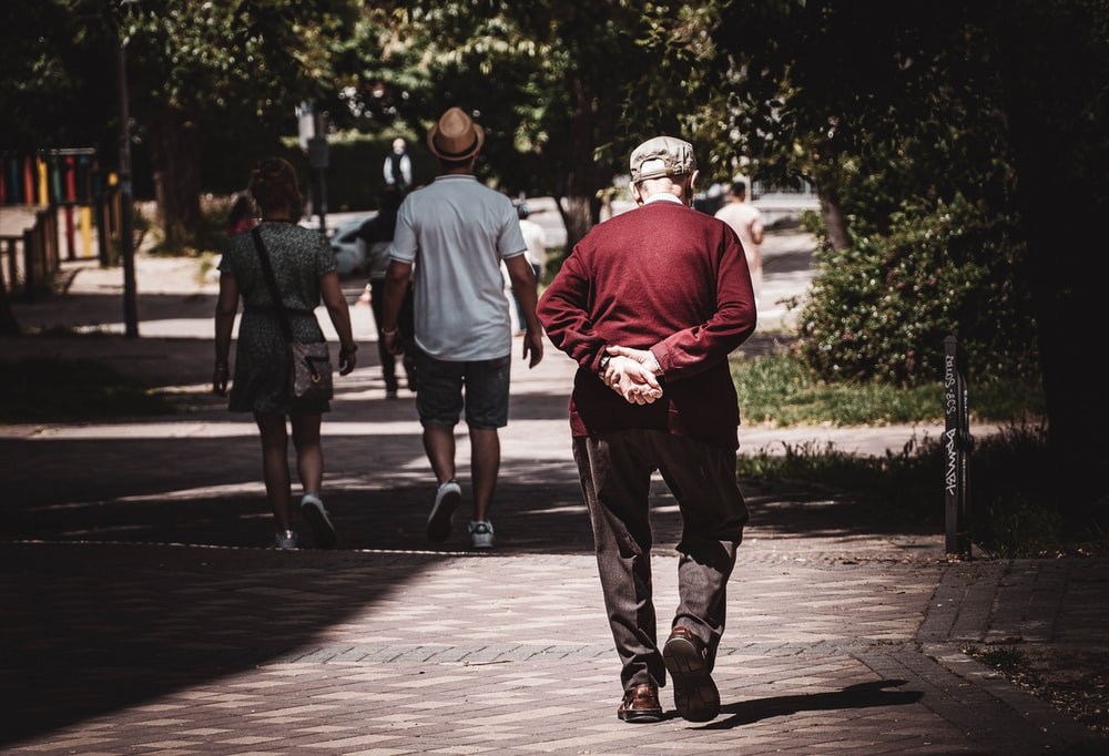 man in red hoodie walking on sidewalk during daytime