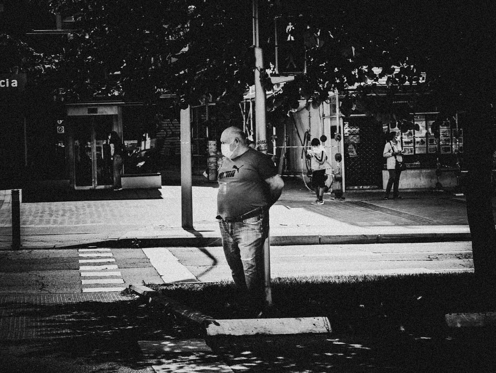 man in black jacket and pants standing on pedestrian lane in grayscale photography