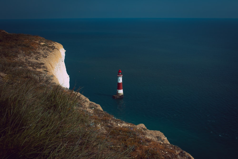 red and white lighthouse on cliff near body of water during daytime