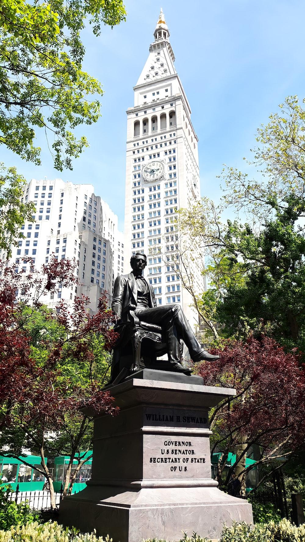 man sitting statue near white concrete building during daytime