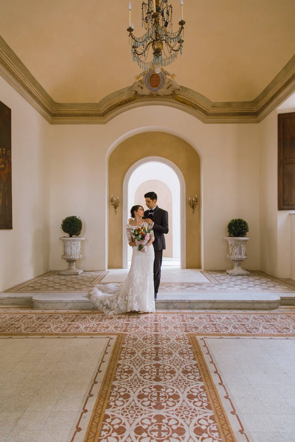 bride and groom standing on white and brown floral carpet