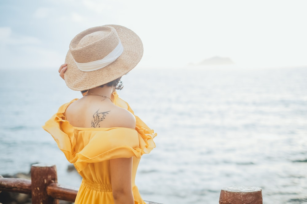 woman in yellow dress wearing white sun hat standing on brown wooden dock during daytime