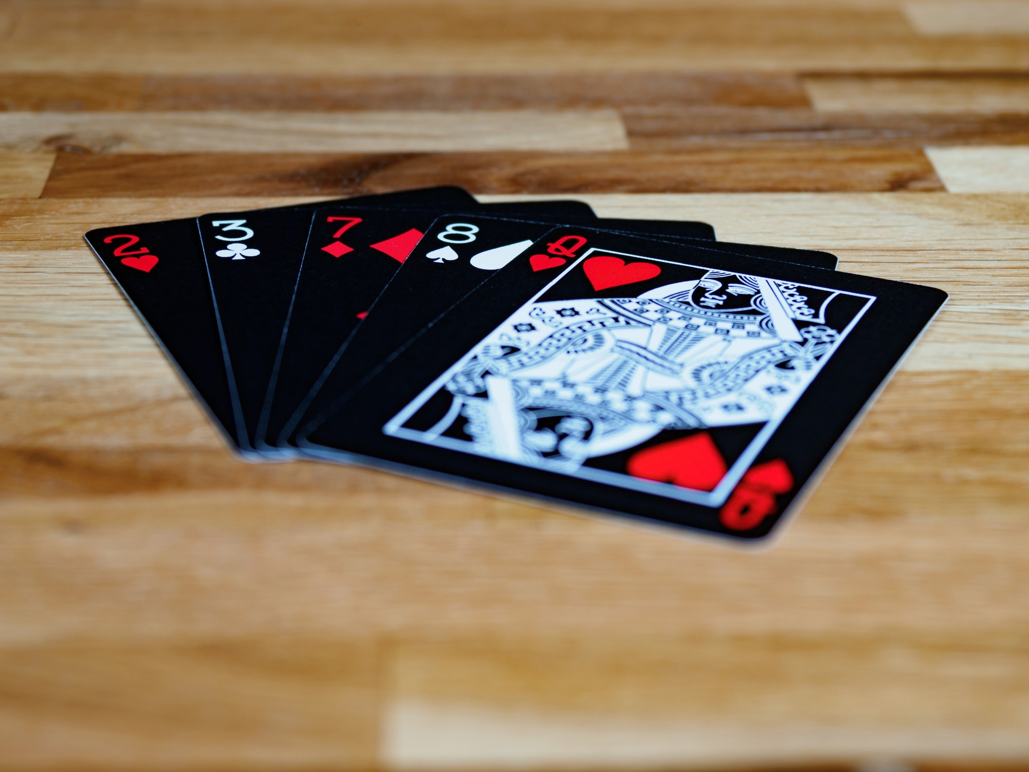 cards, playing cards, gambling, close up, bokeh, wood background, product shot, focus, deal, worst poker hand, throw away hand, poker, bad hand, loser, despair, bad luck, money loss, throw in your chips, gambling,