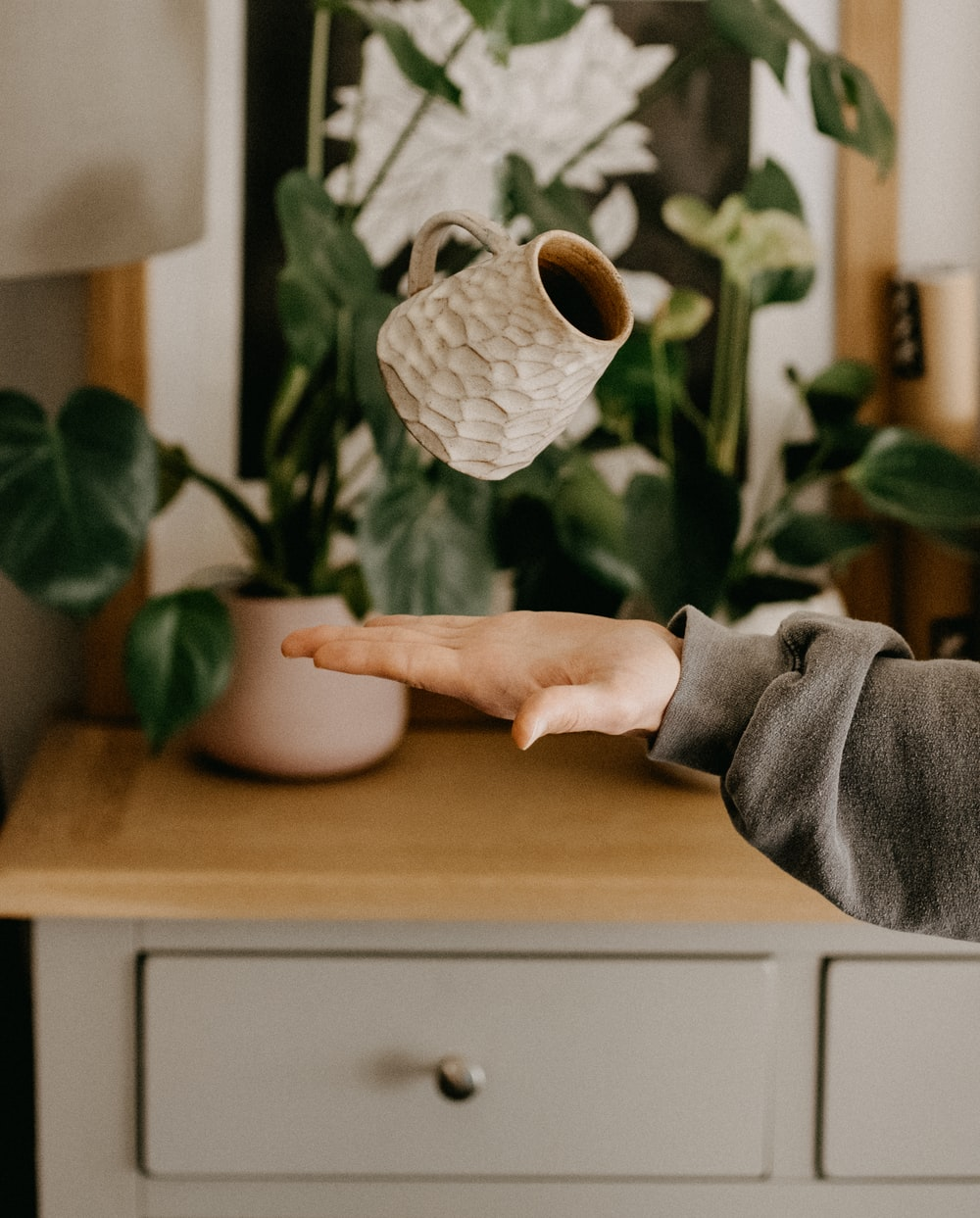 person in gray sweater holding white ceramic vase
