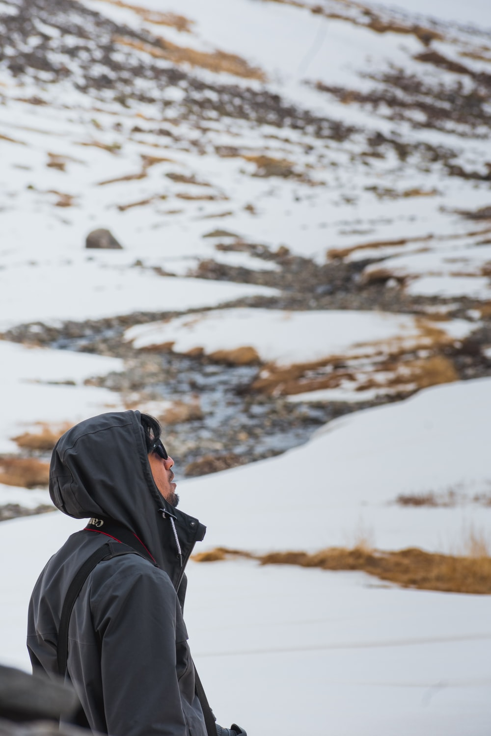 person in black hoodie standing on snow covered ground during daytime