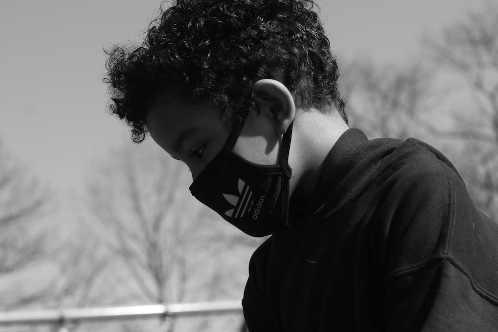 grayscale photo of man in black hoodie