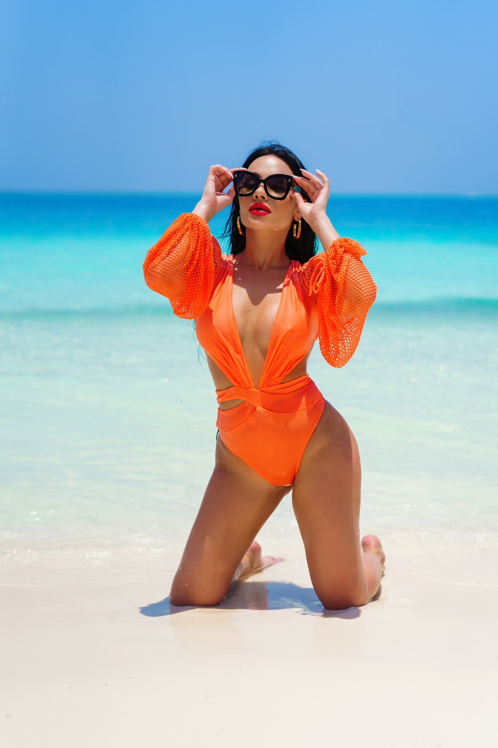 woman in orange one piece swimsuit sitting on beach shore during daytime