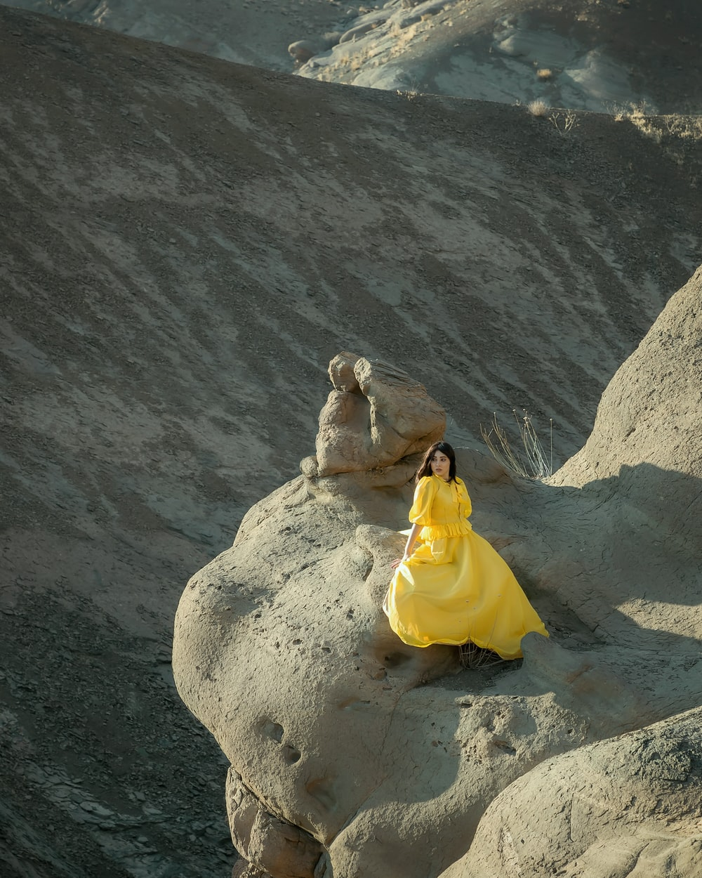 woman in yellow dress sitting on rock formation