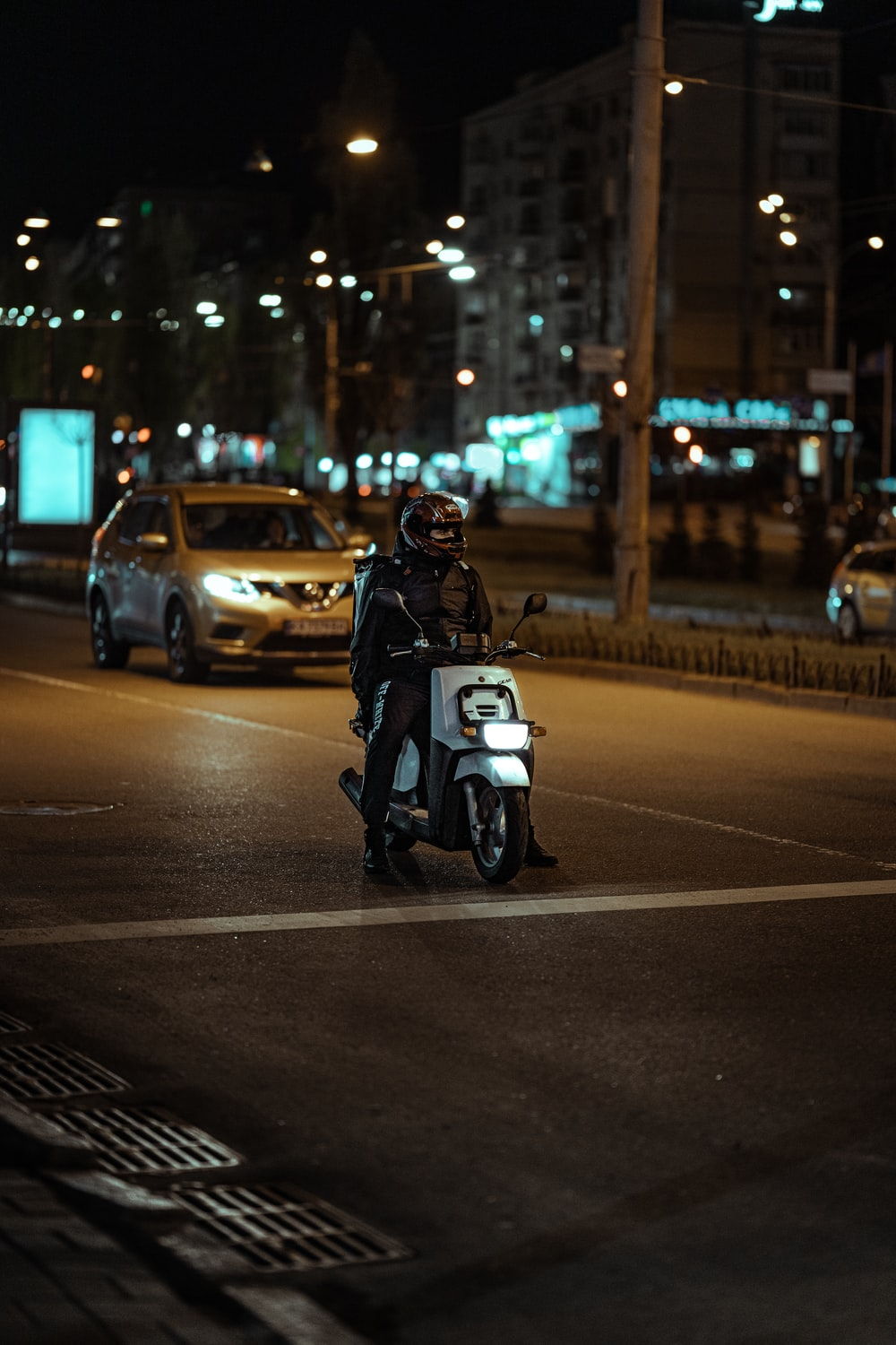 person riding white and black motorcycle on road during night time