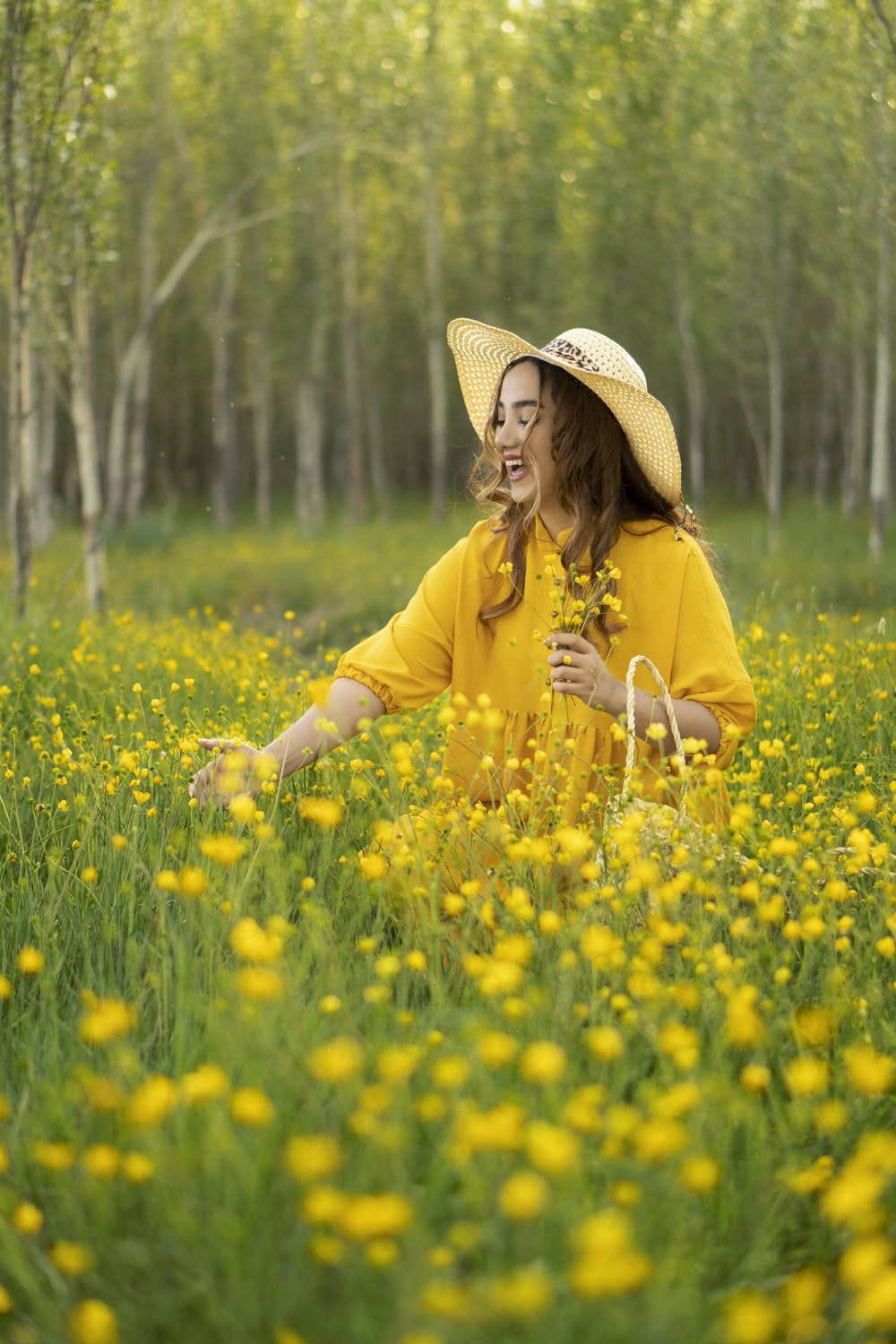 girl in yellow long sleeved shirt and brown cowboy hat standing on yellow flower field during