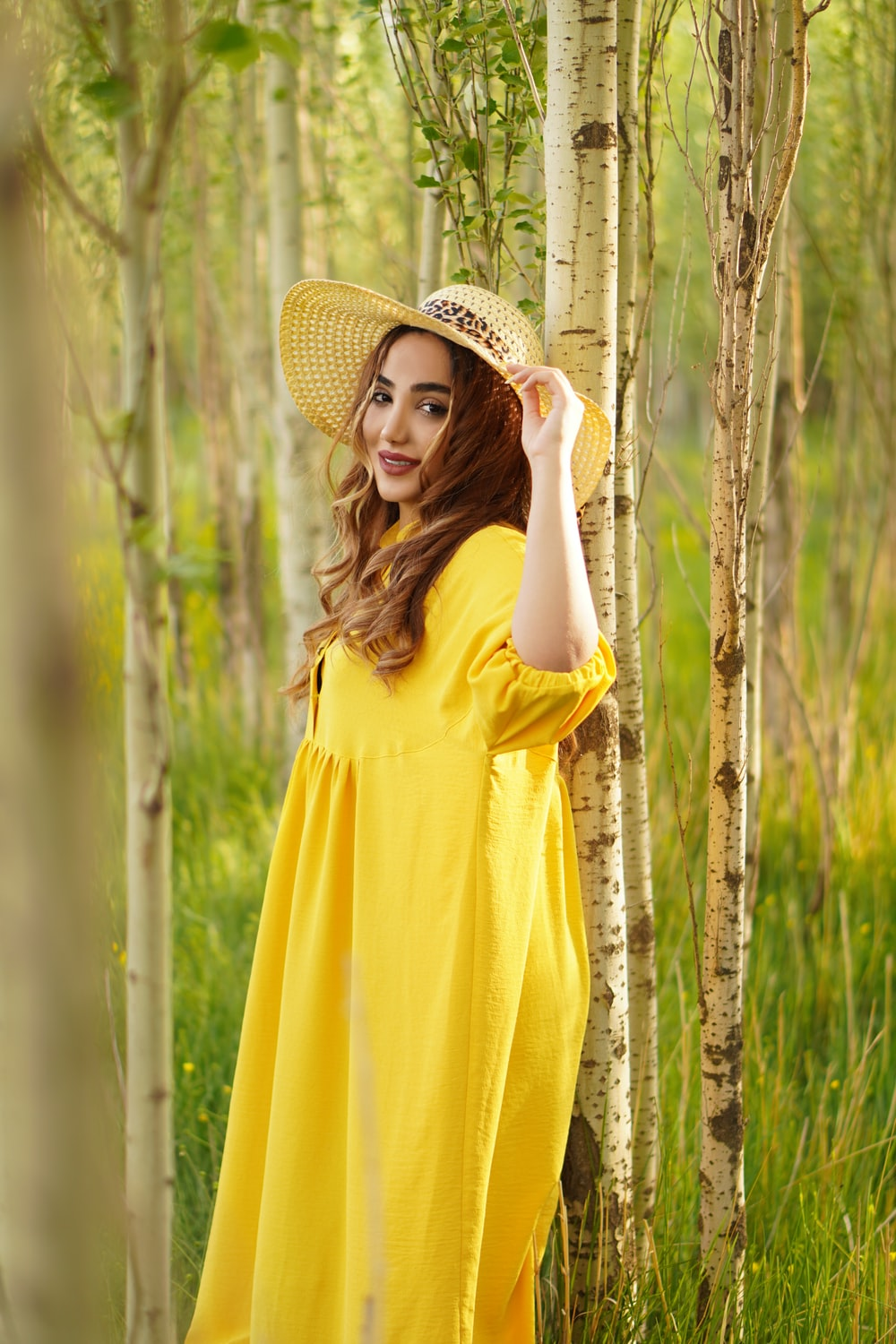 woman in yellow dress wearing brown straw hat
