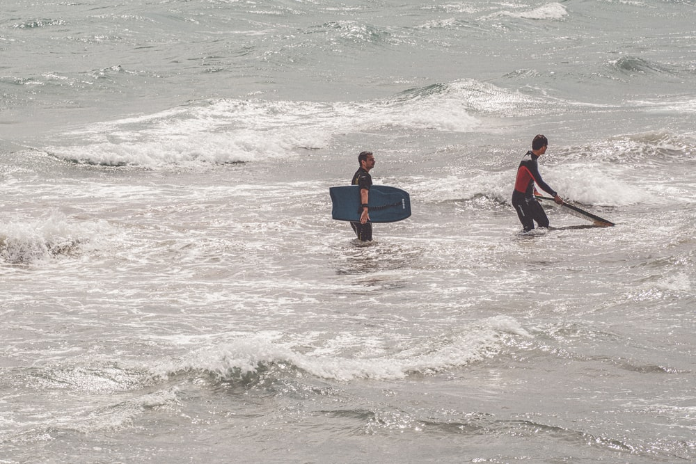 man in black and red wet suit carrying blue surfboard on sea waves during daytime
