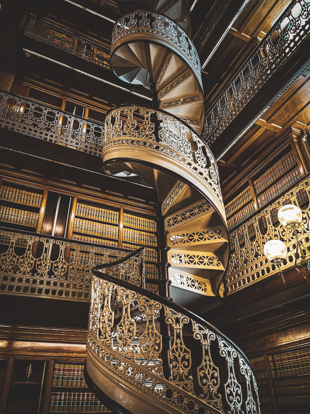 brown wooden spiral staircase with black metal railings