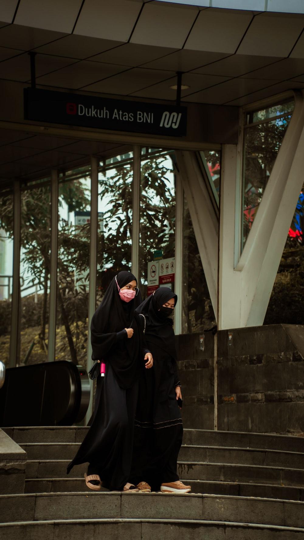 woman in black hijab standing near glass window