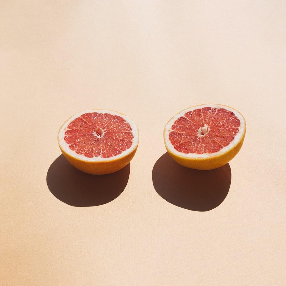 2 sliced orange fruit on white table