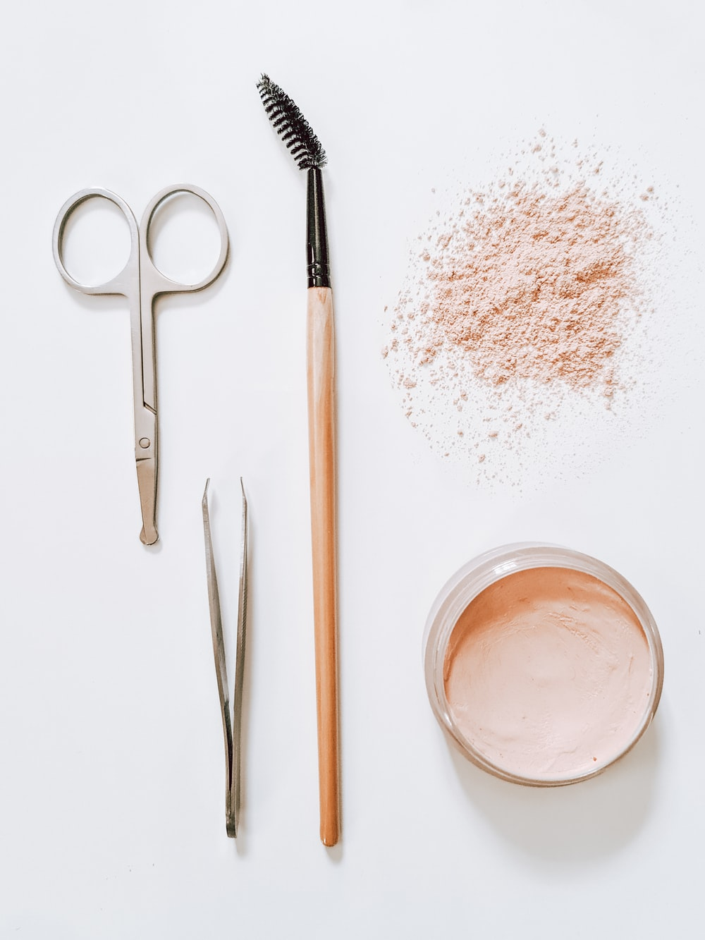 white powder on clear glass jar beside silver scissors