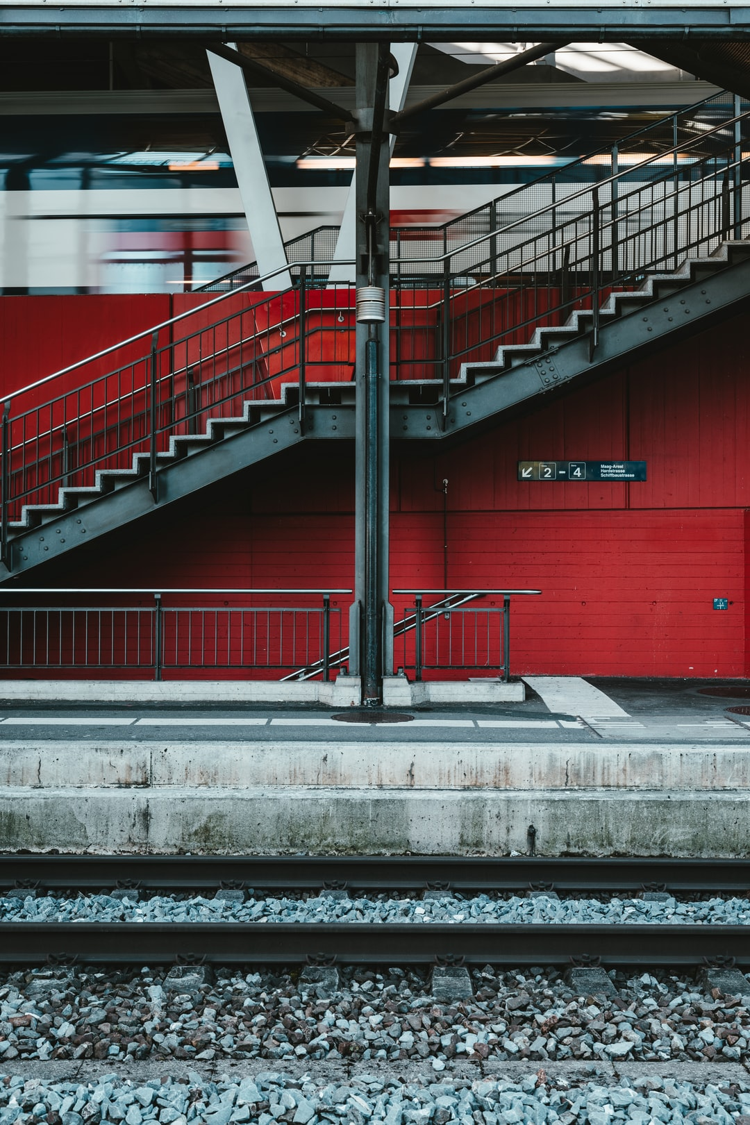 red metal railings on gray concrete stairs