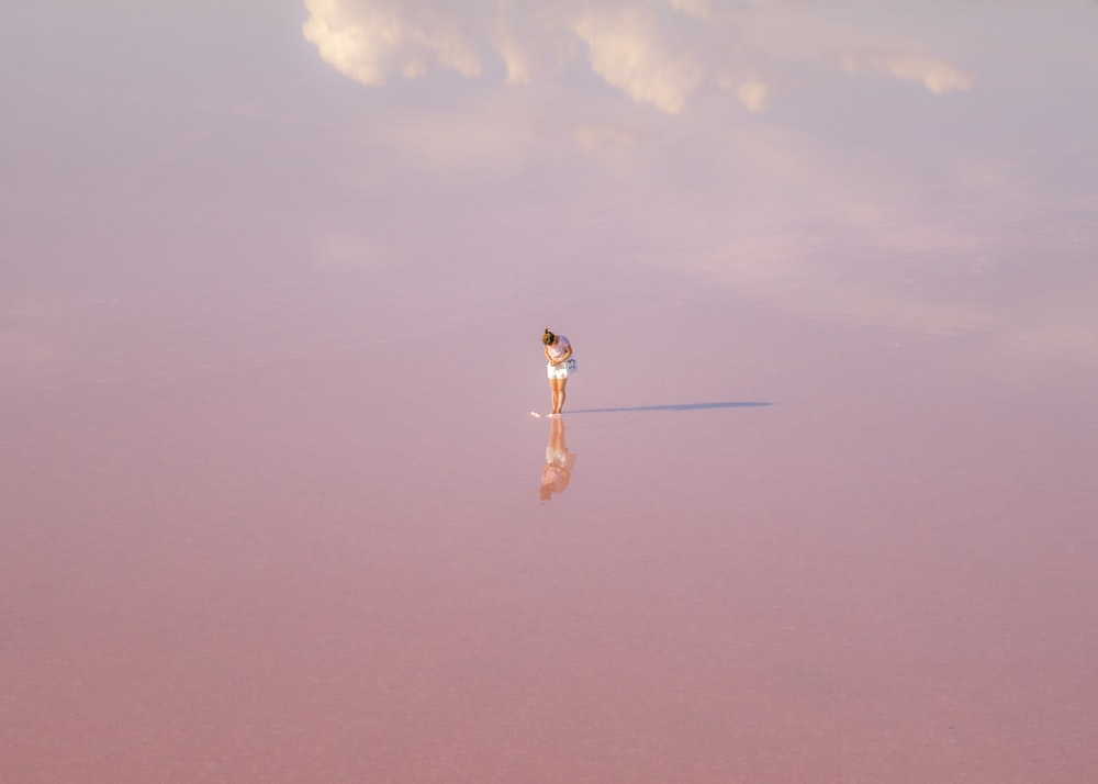 woman in white dress standing on brown sand under blue sky during daytime