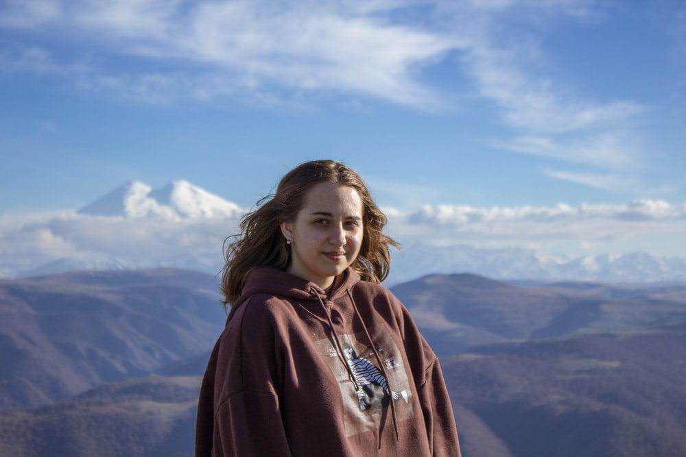 woman in red hoodie standing on top of mountain during daytime