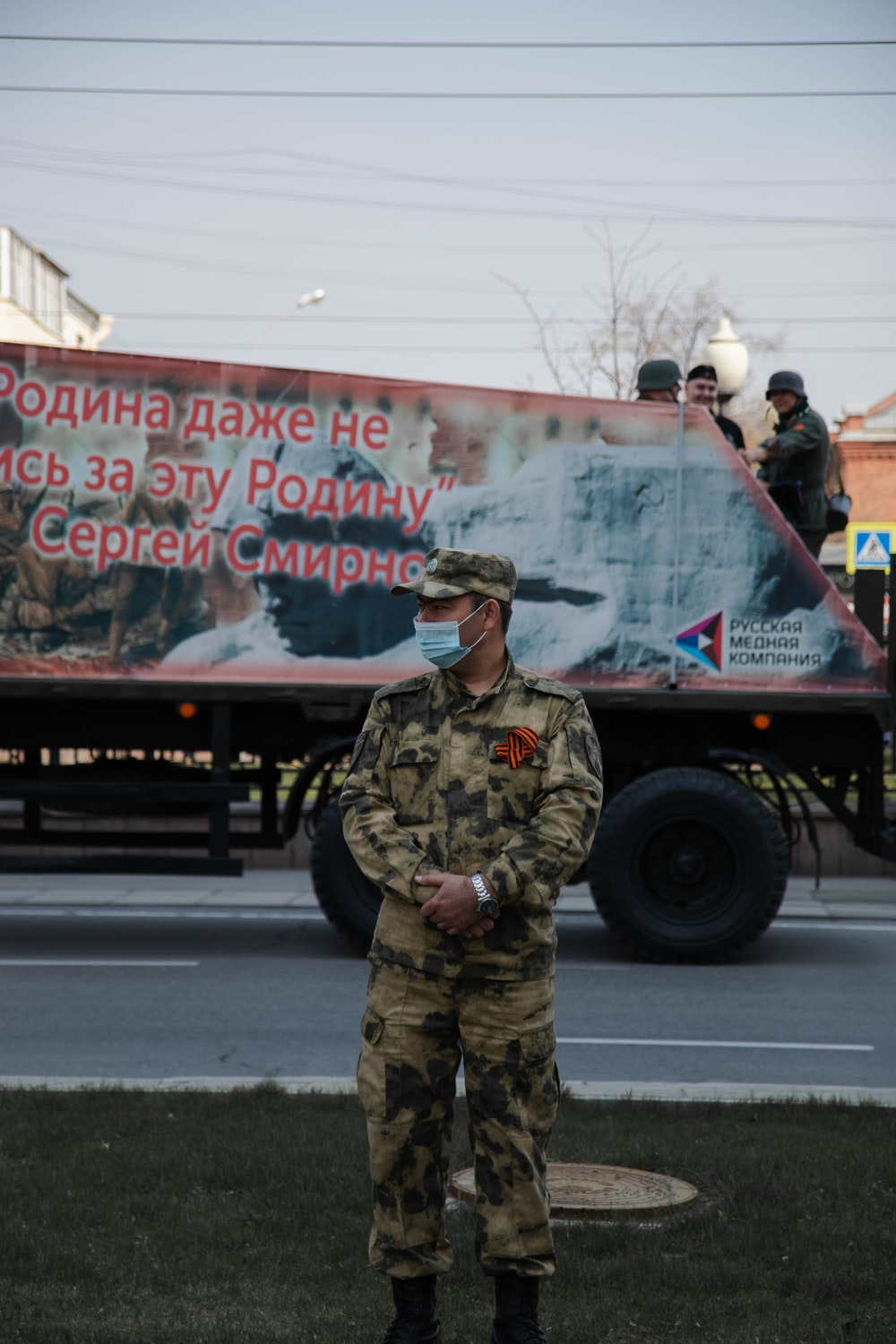 man in green and brown camouflage uniform standing near black truck during daytime