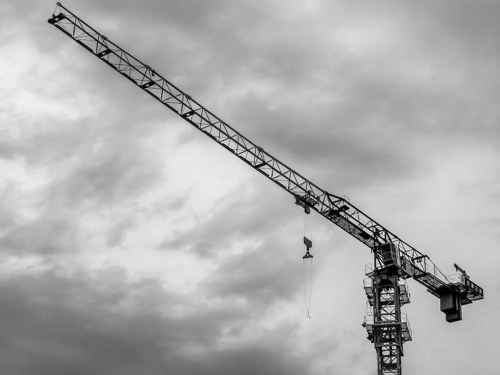 black crane under cloudy sky