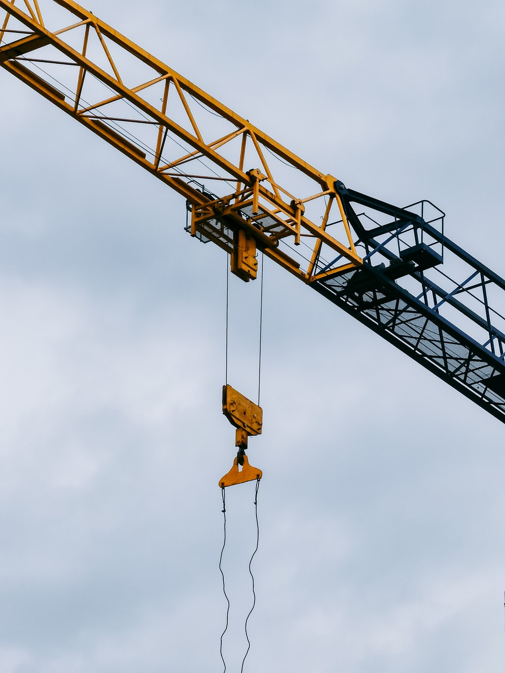 yellow crane under cloudy sky during daytime