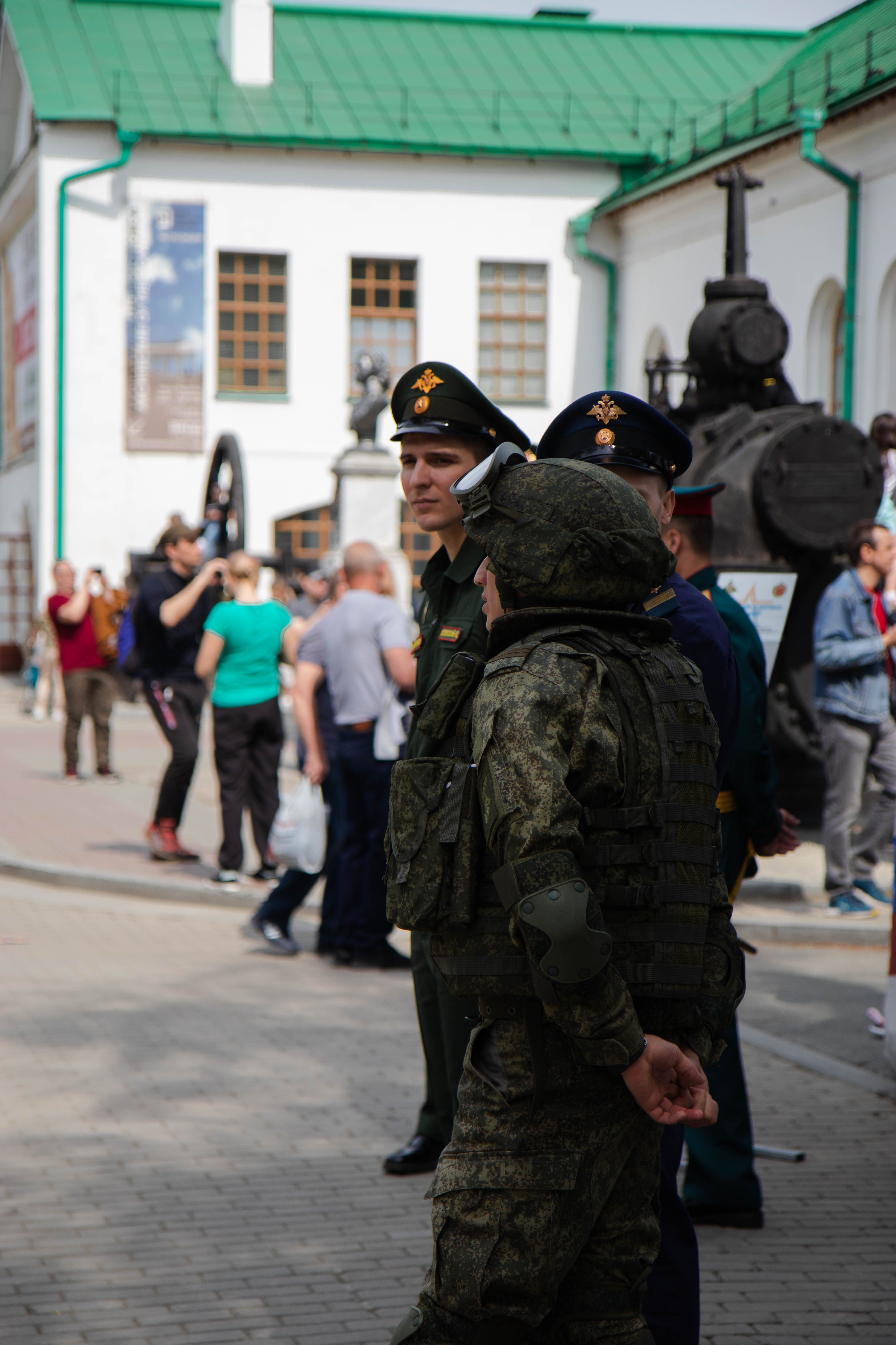 man in black and green camouflage uniform standing on street during daytime
