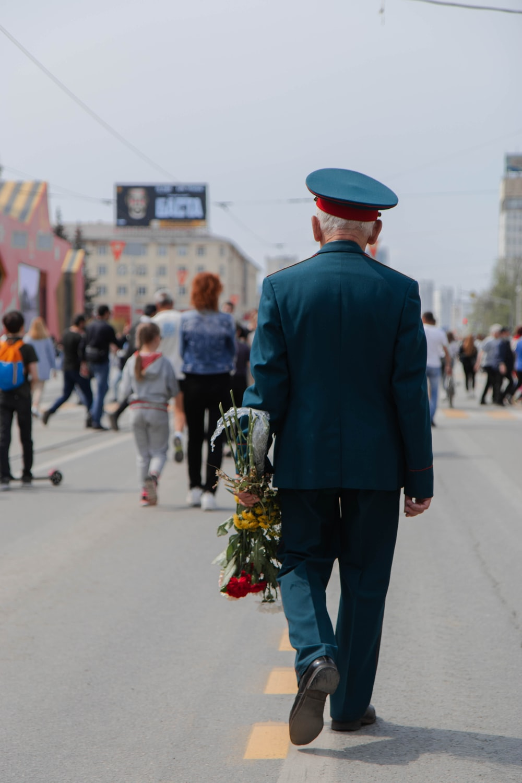man in black suit walking on street during daytime