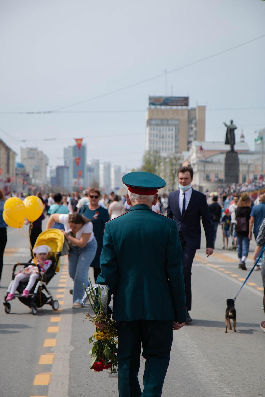 man in green suit walking on street during daytime