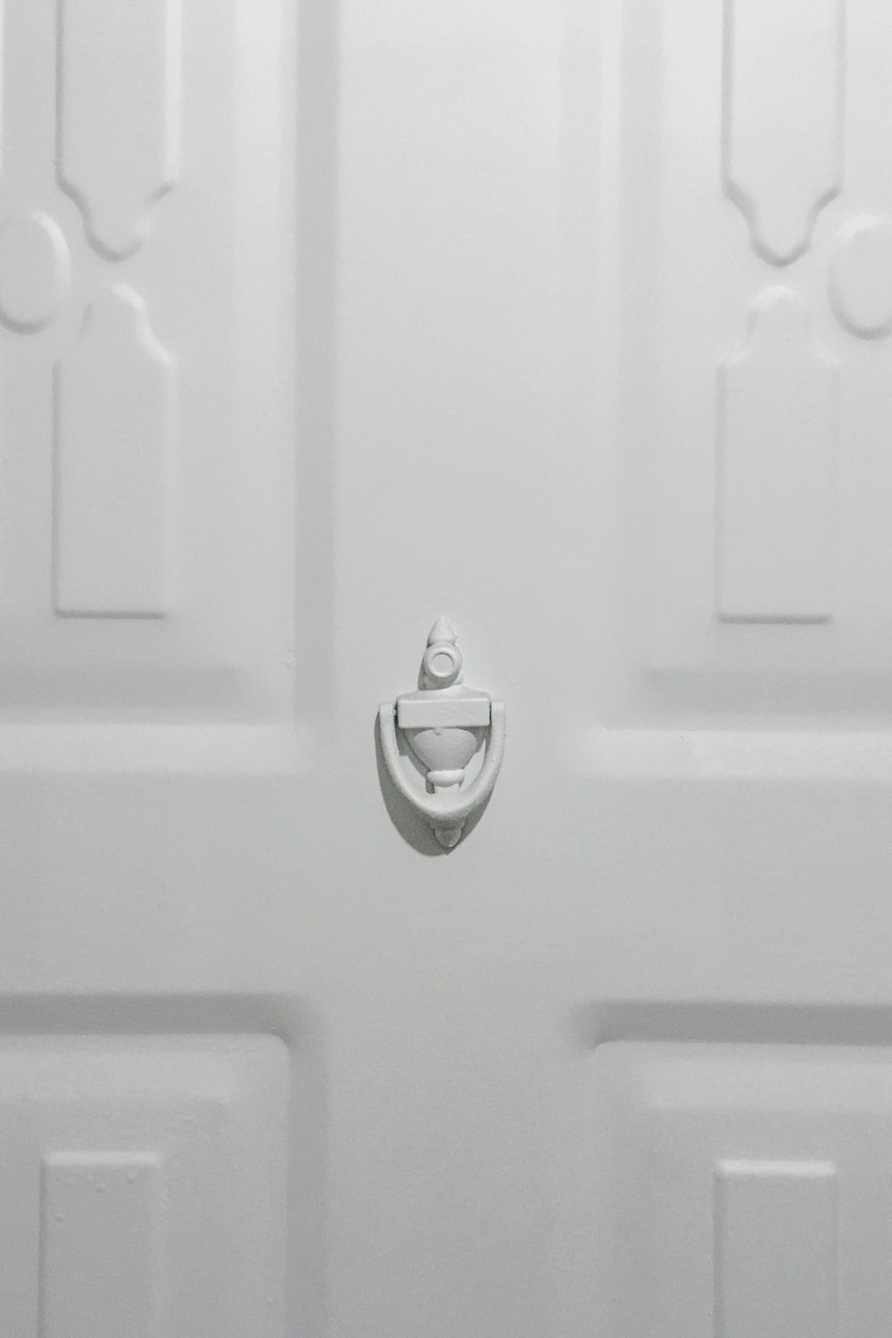 silver heart shaped pendant on white wooden door