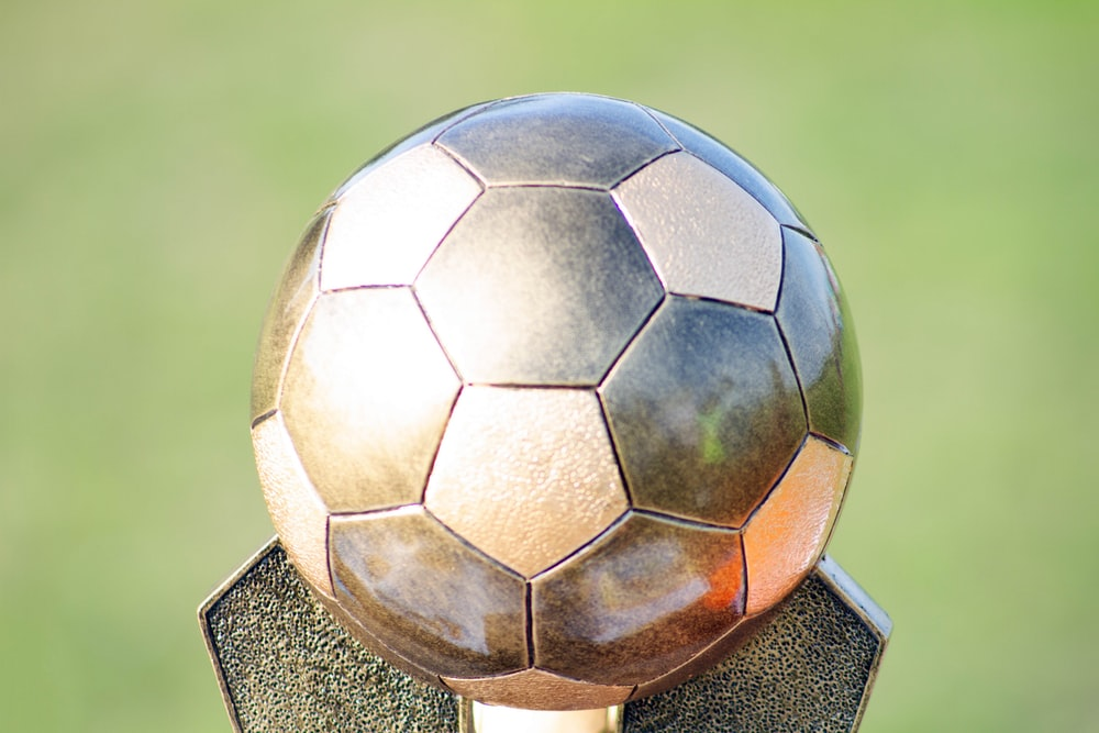 soccer ball on brown wooden stand
