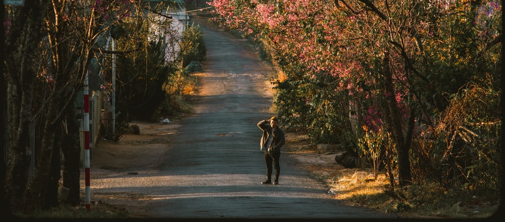 person in black jacket walking on gray asphalt road during daytime