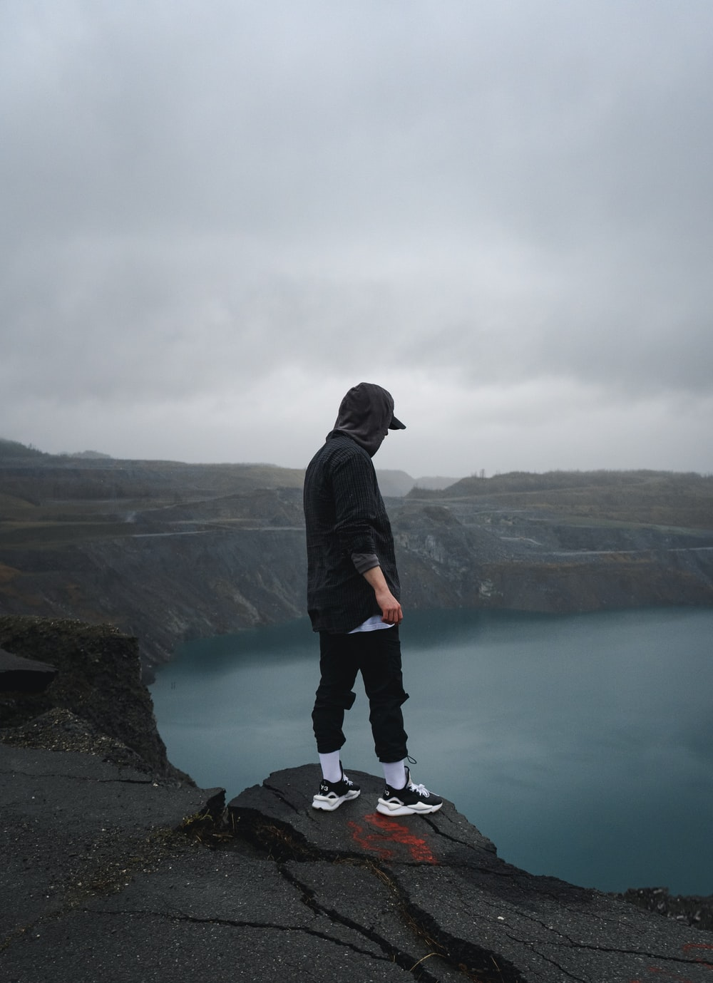 man in black hoodie and black pants standing on rock near body of water during daytime