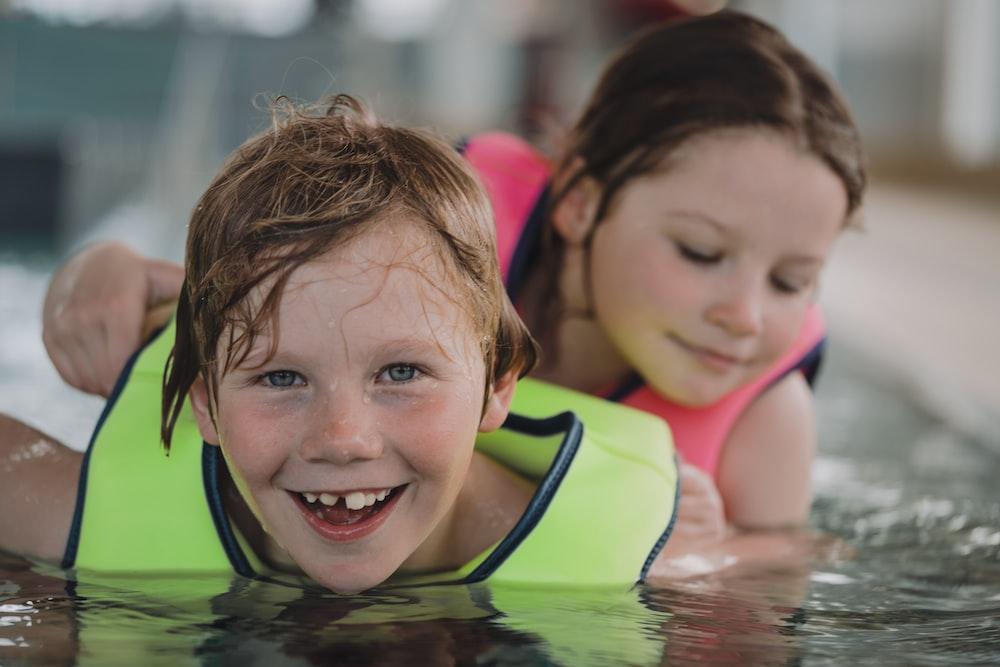 girl in pink tank top swimming on pool during daytime