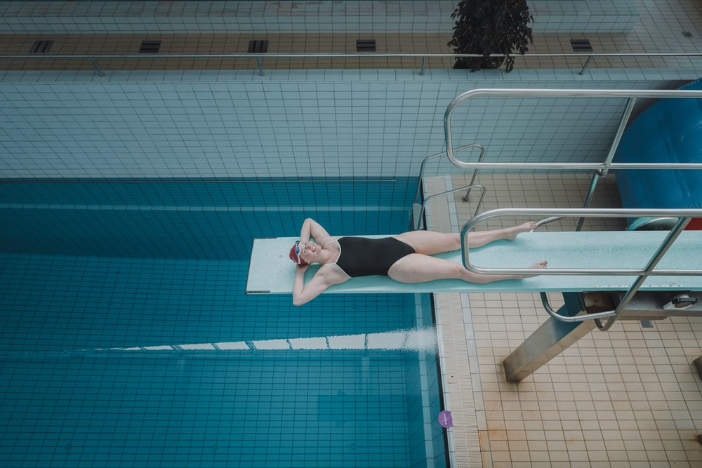 woman in black shorts standing beside swimming pool during daytime