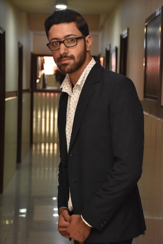 man in black suit jacket wearing eyeglasses