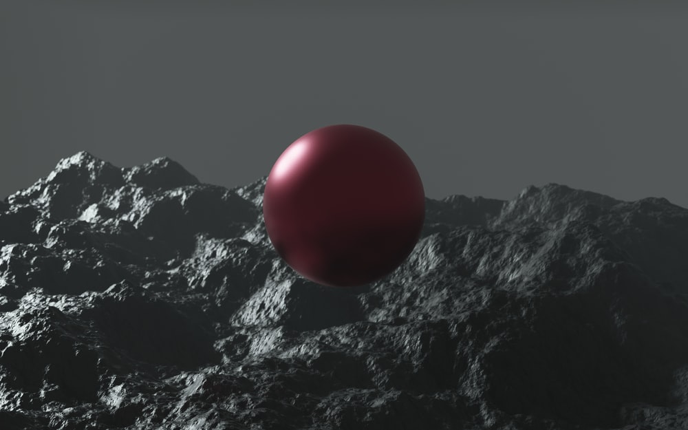 red ball on black and white mountain