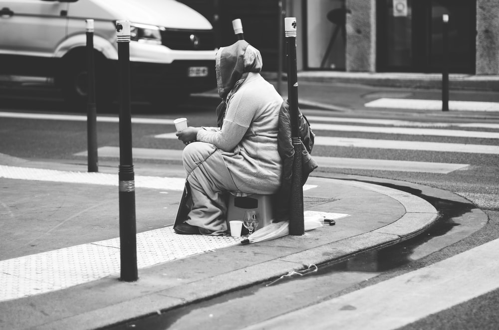 man in gray jacket sitting on bench