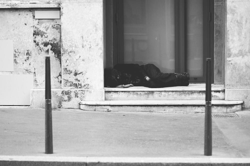 grayscale photo of man lying on floor